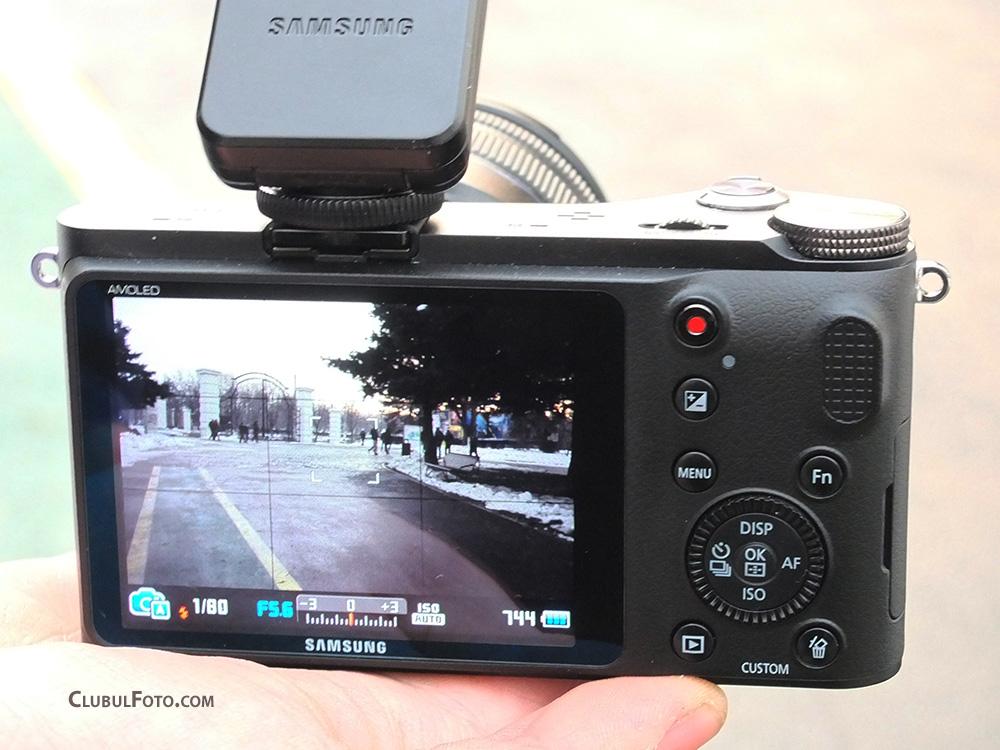 Partea din spate a aparatului dezvaluie ecranul LCD AMOLED, butoanele si rotita de selectie a modurilor de fotografiere.